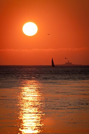 A silhouetted boat gently sails against a lighthouse bathed by a warm and peacefull sunset photo