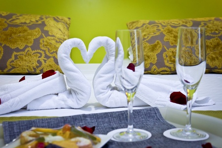 Romantic getaway with rose petals and towels shaped like swans on hotel bed photo