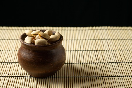 Pistachios in a clay bowl on the table