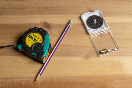 Tape measure and pencil on the background of a piece of wood Stock Photo