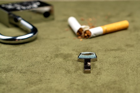 Exemption from smoking. The key on the background of a broken cigarette and an open lock