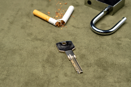 Exemption from bad habits. The key on the background of a broken cigarette and an open lock 版權商用圖片