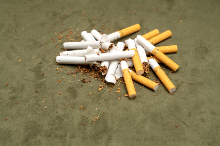 Exemption from smoking. A lot of broken cigarettes on a green background