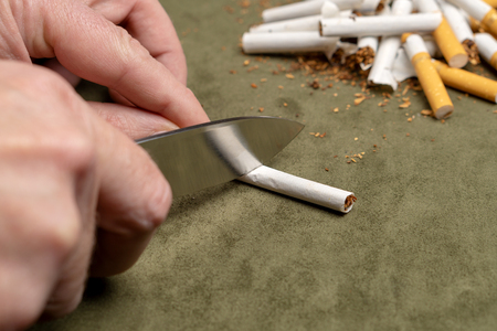 Fighting a bad habit. A man cuts a cigarette with a knife on the background of a pile of broken cigarettes