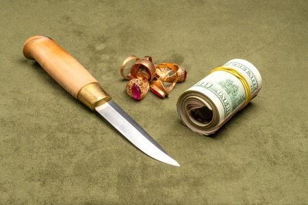 Knife and dollars and gold on a green background