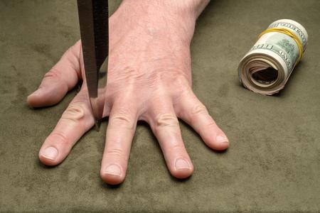 Knife between the fingers of a mans hand Reklamní fotografie