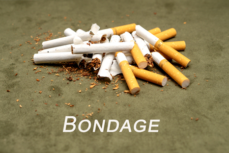 A lot of broken cigarettes on a green background and the inscription Bondage