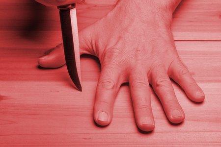 Dangerous game. Blade of the knife between the fingers on the background of a wooden table in red light