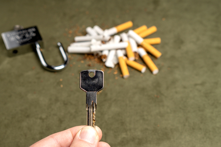 Exemption from smoking. A man holds out a key against the background of broken cigarettes and an open lock