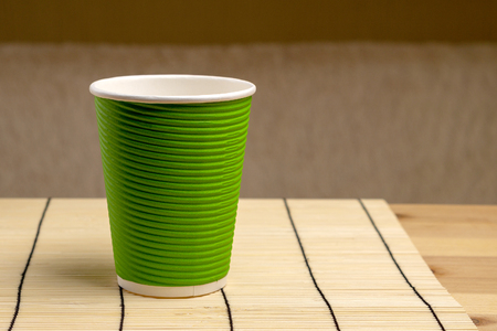 Green paper cup on bamboo stand. Ecological dishes