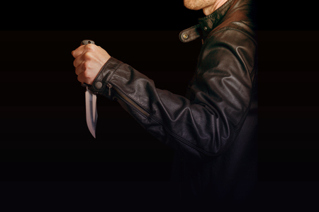 A man in a black leather jacket with a knife in his hand on black background Imagens