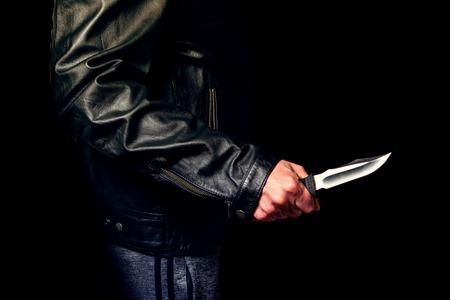 Adolescente amenazado con un cuchillo en la calle, iluminación nocturna