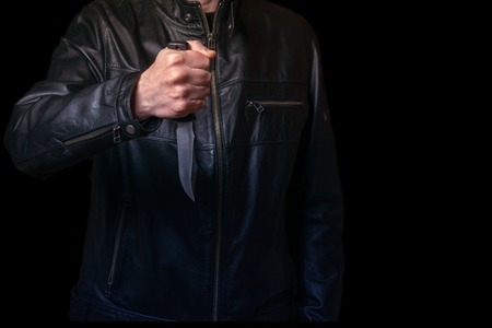 A man in a black leather jacket with a knife in his hand