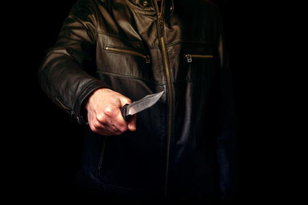 A man in a black leather jacket threatens with a knife