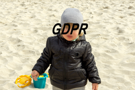 A little boy in a gray hat is playing on the beach, his face is hidden inscription GDPR - concept image.