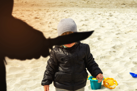 Silhouette of a man with a knife and a child playing in the sand on the beach Stock Photo