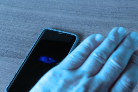 Un hombre está bloqueado por un teléfono inteligente que lo mira con un ojo, el concepto de seguridad cibernética Foto de archivo