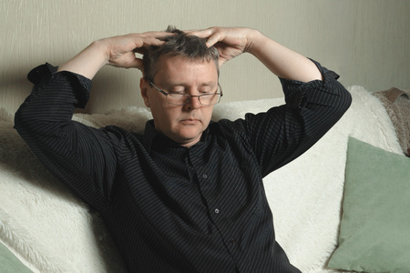 A man with glasses and a black shirt is massaging his head