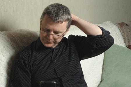 A man in a black shirt reads a message in the smartphone