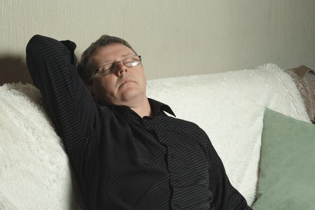A man in a black shirt dozed off on the couch