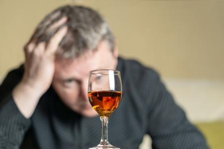 Man out of focus looks at a glass of brandy Imagens