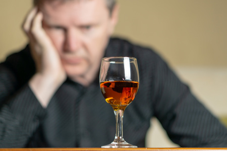 Tired man leaning his head on a glass of brandy. Man out of focus Imagens
