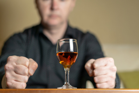 A man sits in front of a glass of brandy. Man out of focus