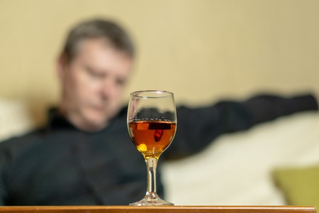 A glass of brandy on the background of a tired man. Man out of focus