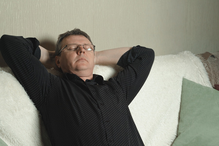 A man with glasses and a black shirt dozed off while sitting