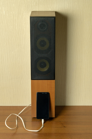 Old speaker linked by usb-cable to smartphone. Progress technology concept Imagens