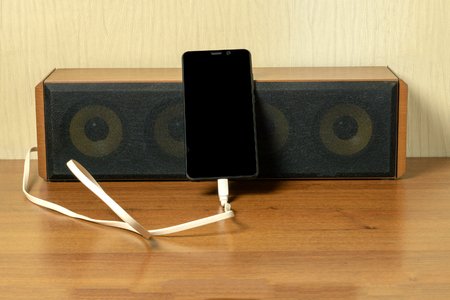Old speaker linked by usb-cable to smartphone