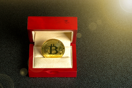 Golden bitcoin in a mahogany box on a black texture background, top view Imagens