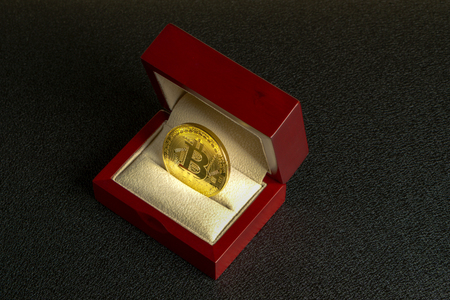 Golden bitcoin in a mahogany box on a black background texture, side view