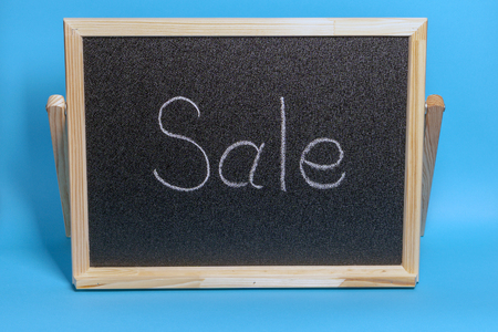 Black Board in a wooden frame on a blue background with the inscription sale. Mockup for shopping, sales, black friday
