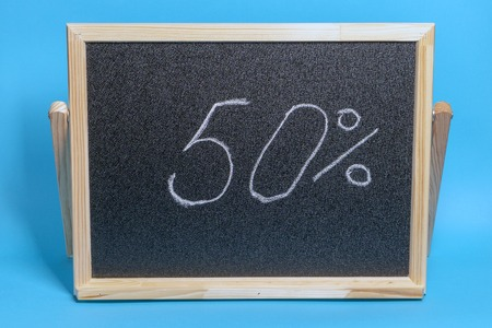 Black Board in a wooden frame on a blue background with the inscription 50 percent. Mockup for sales, black friday