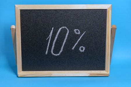 Black Board in a wooden frame on a blue background with the inscription 10 percent. Mockup for black friday