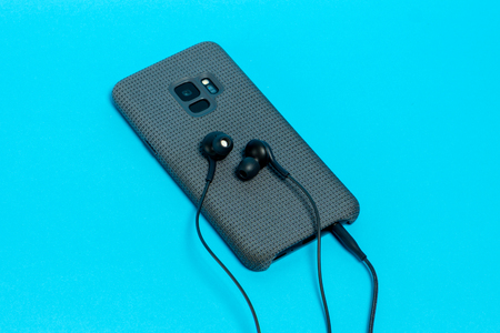 Smartphone in stylish textile case with connected headphones on blue background