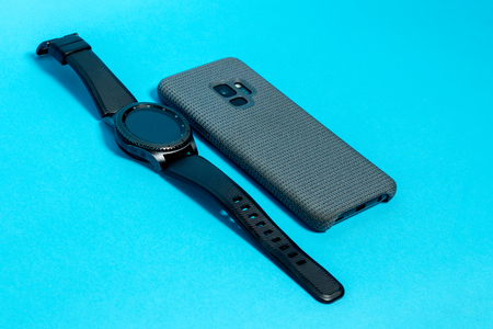 Smartphone in a gray textile case and a smart watch on a blue background Imagens