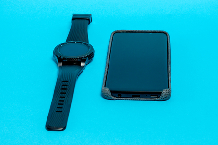 Smartphone in a gray textile case and a smart watch on a blue background. Clouse-up Imagens