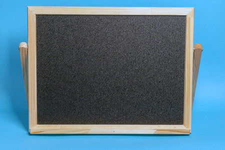 Black Board in a wooden frame on a blue background. Mockup for shopping, sales, black friday
