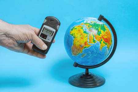 A man measures the level of radiation near the globe.