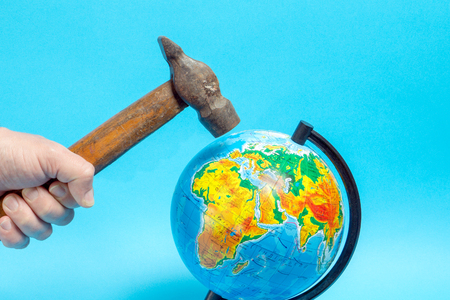 Male hand with an old rusty hammer, swings over the globe.