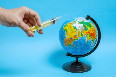 A man holds a syringe with a clear liquid near the globe. Imagens