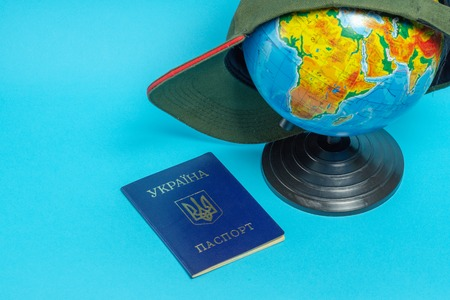 Passport of a citizen of Ukraine near the globe with a baseball cap.