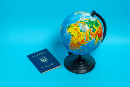 Passport of a citizen of Ukraine near the globe on a blue background.
