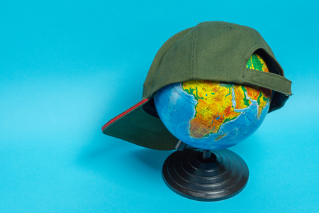 Globe with a green baseball cap on it on a blue background.