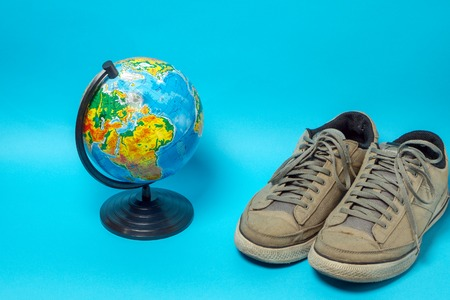 Globe and old worn sneakers in gray on a blue background.
