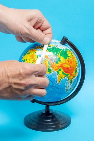 Male hand putting a patch on a globe.