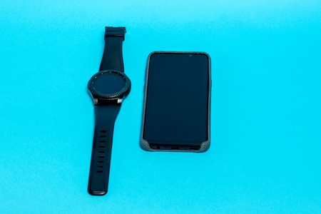 Smartphone in a gray textile case and a smart watch on a blue background.