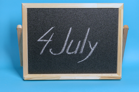 Blackboard with the word chalked 4th of july on blue background Imagens